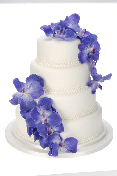 Eric-Lanlard-4-tiered-iced-white-with-pearl-detail,-dressed-with-orchids