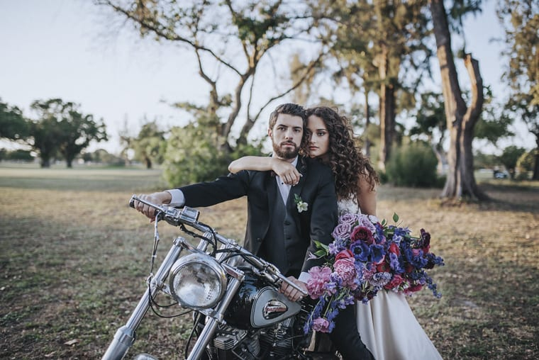 Bride with purple and pink wedding bouquet with husband on motorbike in the countryside