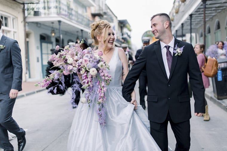 Bride with lilac and purple wedding bouquet and husband in busy street