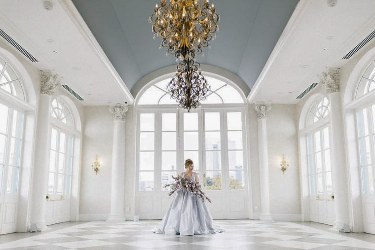 Bride with pastel wedding bouquet in white ballroom with chandeliers