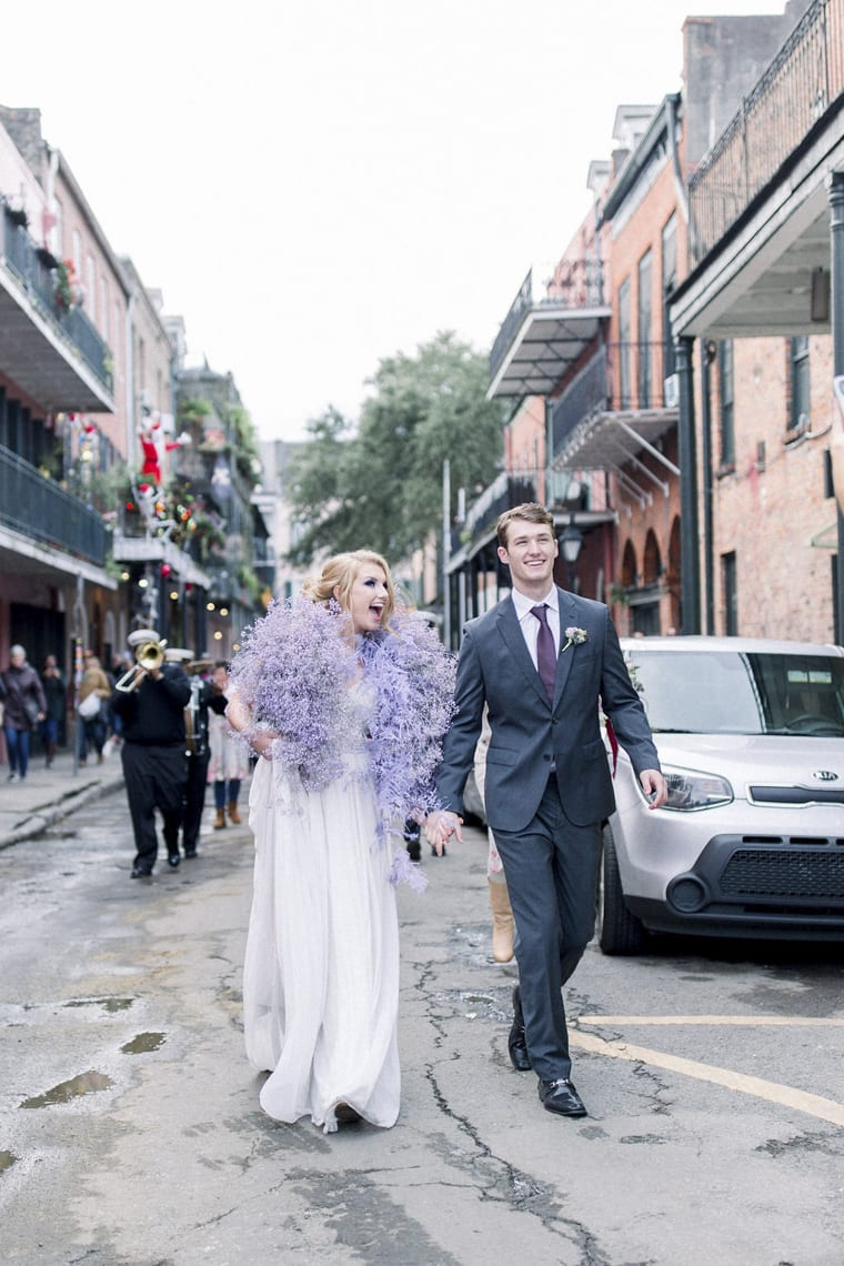 Bride with lilac floral stole and husband walking down a busy street