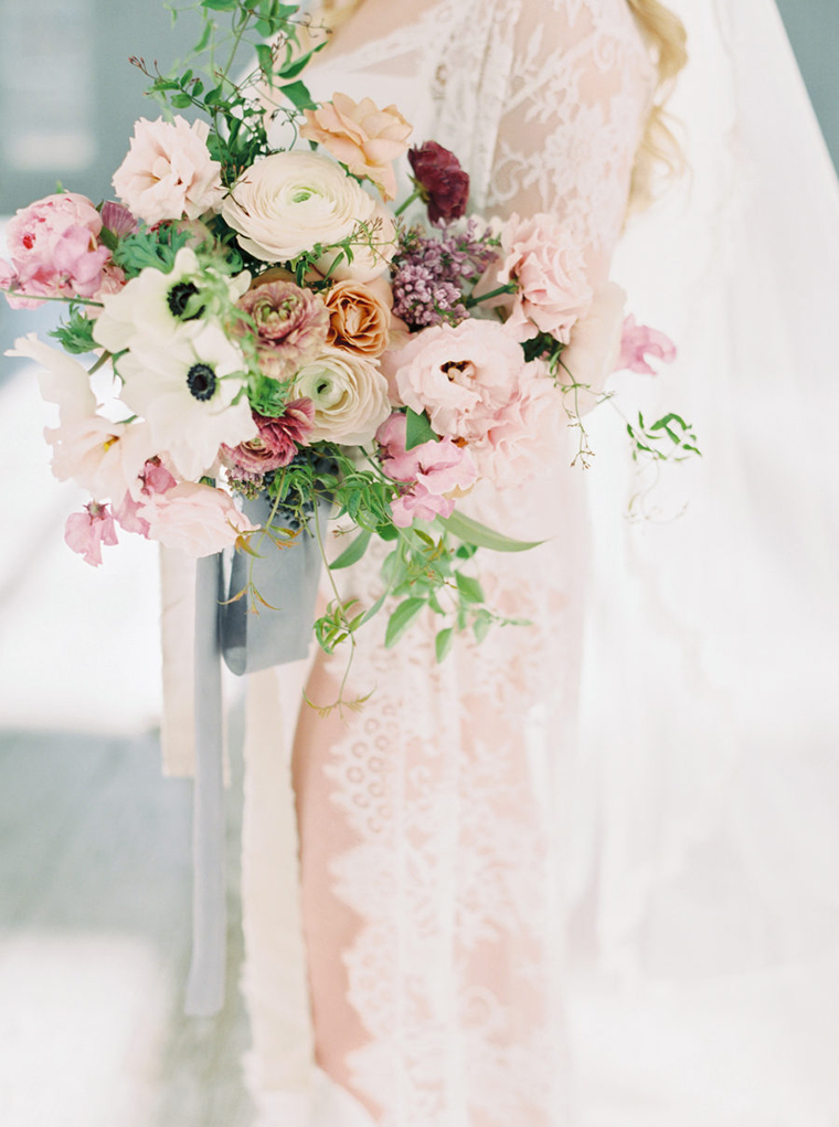 White pink and apricot bridal bouquet featuring ranunculus, anemones, sweet peas and roses by Moss Floral Design Photographer Stephanie Brazzle
