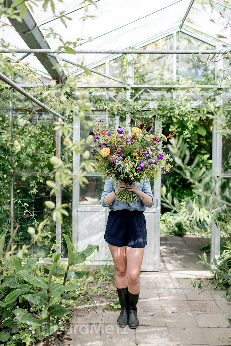 Girl holding bouquet of flowers in greenhouse.